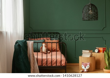 Real photo of a cute, green and orange bedroom interior for a kid with plush fox toys, molding on green wall and books on bedside table