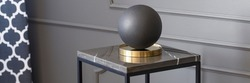 Real photo of a decorative ball standing on a table in living room interior with molding on the wall