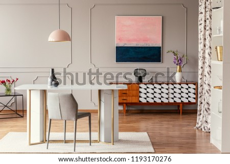 Real photo of a dining room interior with a table, pink painting and vintage cabinet