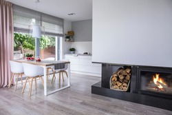 Real photo of a fireplace in a modern kitchen and dining room interior. Empty wall, place for your painting