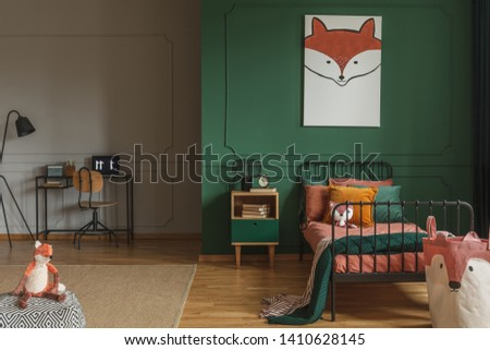 Real photo of a fox painting hanging on a green wall with molding, above black, metal bed in a kid's room interior