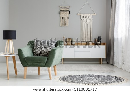 Real photo of a green armchair standing in a bright, natural living room interior with macrame hanging on gray wall above white cupboard