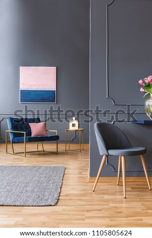 Real photo of a grey, spacious living room interior with a wooden floor and grey rug next to a chair and in front of the other, wider blue chair