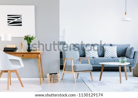 Real photo of a living room interior with study space. Typewriter on a wooden desk next to a sofa with two white cushions and houndstooth pattern armchair #1130129174