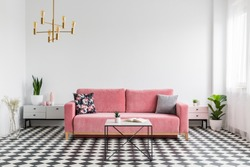 Real photo of a modern living room interior with a checkered floor, pink couch, coffee table and empty, white wall. Place your graphic here