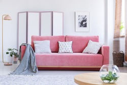 Real photo of a pink couch with white pillows and a blanket standing in a cozy living room interior with a table, a vase, a lamp and a screen