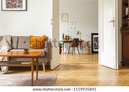 Real photo of a retro living room interior and view of a home office. View through a door