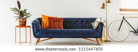 Real photo of a simple living room interior with orange cushions on a navy blue sofa standing between a metal table and golden lamp #1111647605
