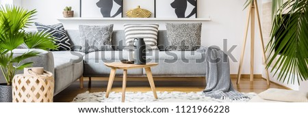 Real photo of black jug and white candle placed on small wooden table standing on fluffy carpet in bright living room interior with corner grey couch and fresh plants