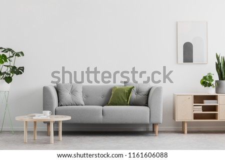 Real photo of grey lounge with green cushion, wooden coffee table, simple poster on the wall and cupboard with books in bright sitting room interior