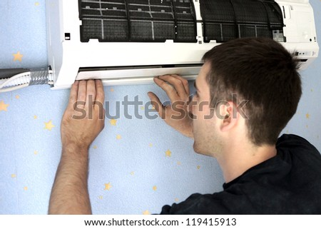 real photo of installation of the conditioner, the worker establishes the internal module