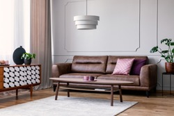 Real photo of light grey sitting room interior with window with drapes, leather sofa with pillows, coffee table on carpet and cupboard with decor