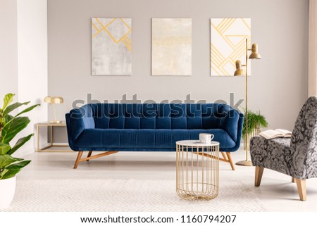 Real photo of marble and gold end table placed on carpet in light grey sitting room interior with three paintings on wall, gold lamps and royal blue couch #1160794207