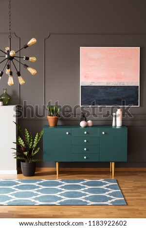 Real photo of moroccan trellis carpet placed on wooden floor in dark living room interior with green cupboard with decor, painting on wall and fresh plants