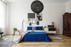 Real photo of navy blue bedroom in modern condo. Dark wooden china closet in the corner, small white dresser with vintage radio on it next to king size bed with velvet pillows and blanket.