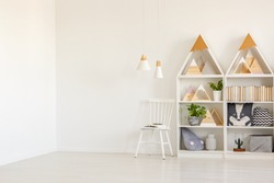 Real photo of white kid room interior with two lamps, mountain shape rack with books and decor and empty place for your bed
