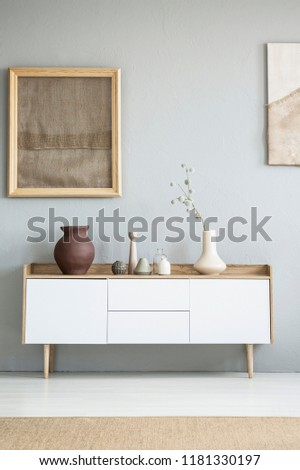 Real photo of white wooden cupboard with vase with flowers and decor standing in bright grey living room interior with poster with cloth
