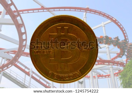 real physical bitcoin with roller coaster in background to illustrate the up and down nature and volatility of crypto currencies #1245754222