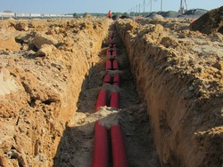 Real process of construction on a building site, laying orange pipes, debris, autumn, trench, view of underground utilities, dug pipes, pouring foundation, Rusted gas and oil pipeline