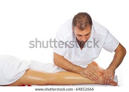 Real professional masseur giving therapeutic massage to woman's legs