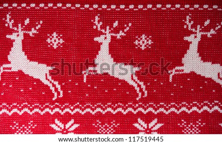 Real red knitted background with white Christmas deers and snowflakes