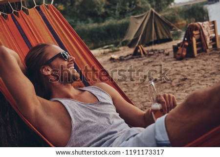 Real relaxation. Handsome young man keeping hand behind head and smiling while lying in hammock #1191173317
