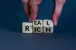 Real rich symbol. Businessman turns wooden cubes with words 'Real rich'. Beautiful grey background. Real rich and business concept. Copy space.
