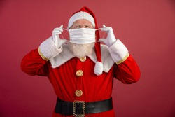 Real Santa Claus with a red background, wearing a protective mask, glasses and hat. Christmas with social distance. Covid-19