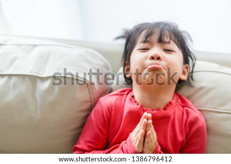 Real shot of regretful kid girl looks gloomy and desperate, keeps palms together, beggs for forgiveness in her mother at home, feels sorry and guilty. Cute adorable asian girl pleads about something.