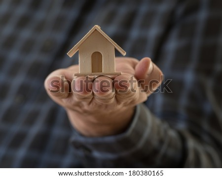 Real state concept. Man holding a small house in his hand