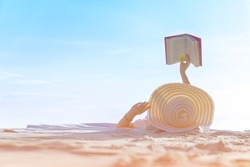 Real view of woman lying on beach, reading book, relaxing on sand. Russian woman in bikini and sun hat, relaxing at sunny, blue sky clear water, remote tropical beaches and countries, travel concept.
