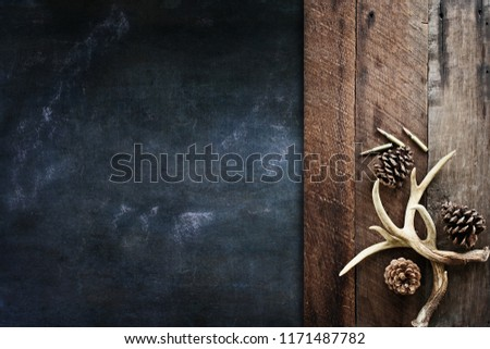 Real white tail deer antlers used by hunters when hunting to rattle in other large bucks over a rustic wooden table over a black background with pine cones and .308 rifle shells. Free space for text.