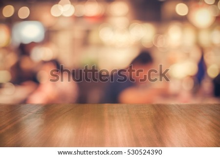 Real wood table with light reflection on scene at restaurant, pub or bar at night. Blurred background for product display or montage your products with several concept idea and any occasional.