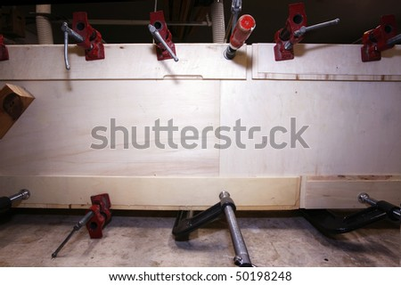 Real woodworking shop: clamps holding workpiece gluing.  Can be used as place for advertisement