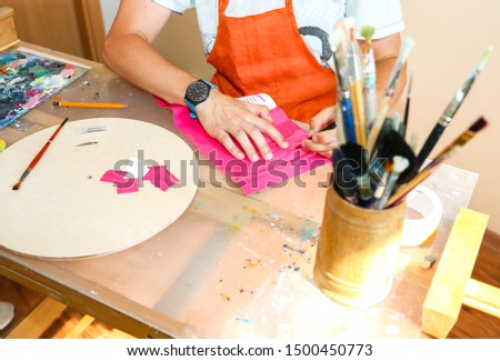 Real work studio of the painter. Man is creating picture. Artist concept. Creative atmosphere. Paint brushes.