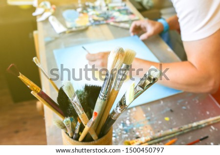 Real work studio of the painter. Man is creating picture. Artist concept. Creative atmosphere. Paint palette knife. Brushes.