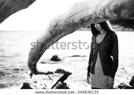 Real young girl in casual clothes near the sea with dead tree over her head. black and white