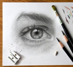 Realistic drawing of a human eye with art materials