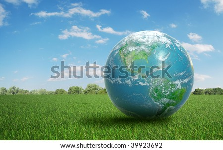 Realistic Earth on a green  field of grass
