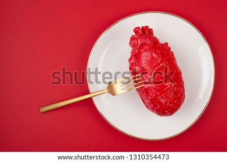 Realistic heart on the dining table in the plate. Love, marriage, proposal, heartbreaker humoristic concept #1310354473