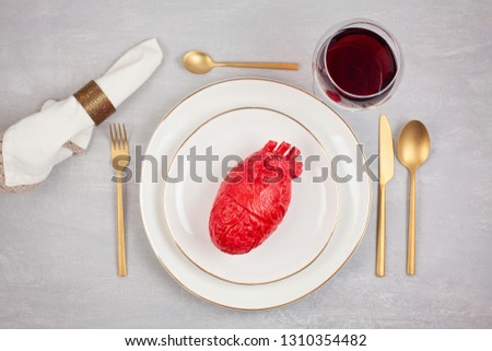 Realistic heart on the dining table in the plate. Love, marriage, proposal, heartbreaker humoristic concept #1310354482