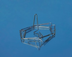 Realistic metal paper clip isolated on blue glass background. Page holder, binder. Realistic paper clip attachment with reflection of glass. paperclip. Attach business document files.