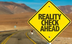 Reality Check Ahead sign on desert road
