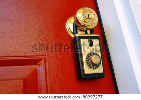 Realtor combination lock box safety key holder on doorknob of a house for sale entrance door for a real estate resale transaction