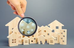 Realtor examines houses through a magnifying glass. Review of the real estate market, search for the best offers based on the criteria of price, location, area, infrastructure. Customer preferences.