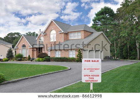 Realtor For Sale Sign on Front Yard Lawn of Large Three Car Garage Suburban Brick McMansion Home in Residential Neighborhood on Cloudy Blue Sky Day