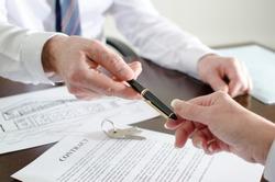 Realtor giving a pen to sign a contract