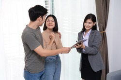 Realtor offer the house and showing young Asian couple with real-estate agent visiting around house for sale