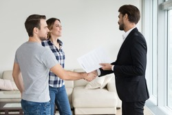 Realtor or landlord handshaking couple buyers tenants make real estate deal holding rental agreement or sale purchase contract, agent and clients shake hands welcoming renters in new home apartment