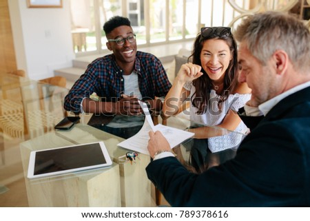 Realtor showing terms of contract to happy couple in office. Real estate agent sharing property details with clients.